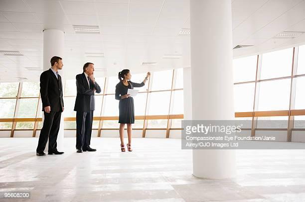 three professionals standing in large open room  - 商業不動産 ストックフォトと画像