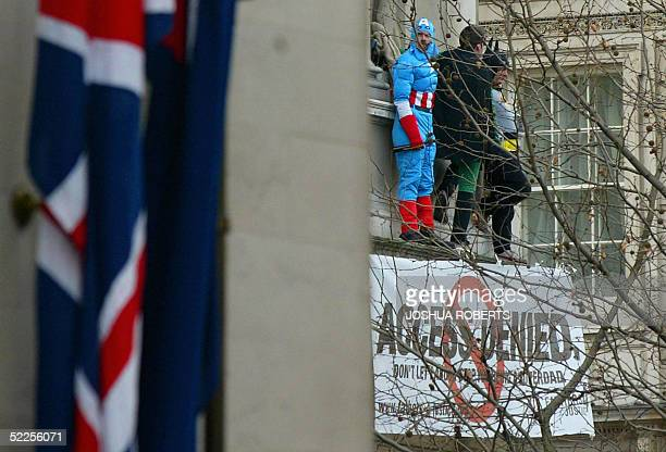 Three protesters from the campaign group Fathers 4 Justice dressed as Captain America , Robin and Batman wave from a balcony on the Foreign Office...