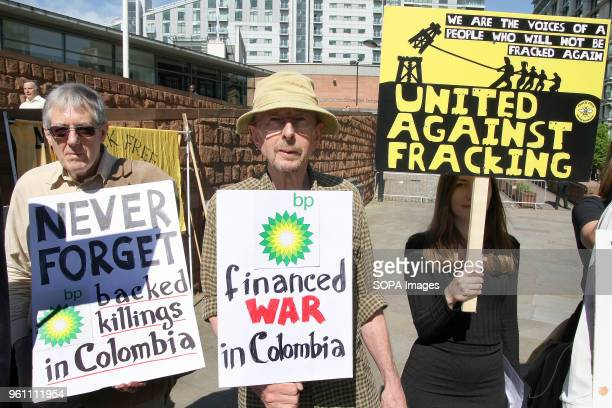 Three Protesters hold placards one which reads 'BP Financed War in Colombia' at a Demonstration outside the BP company's AGM to highlight the...