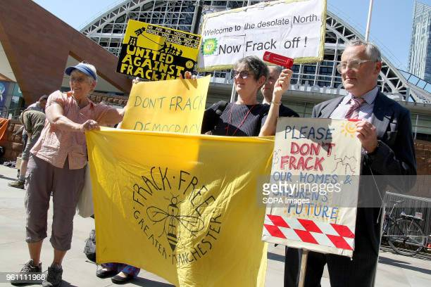 Three Protesters hold placards one which reads Welcome to the Desolate North Now Frack Off at a Demonstration outside the BP company's AGM to...