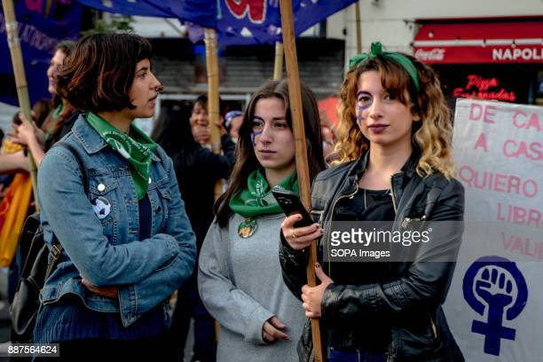 Three protestors hold banners with the symbol of Venus painted on their faces as they wait for the protest to begin Marching from the nation's iconic...