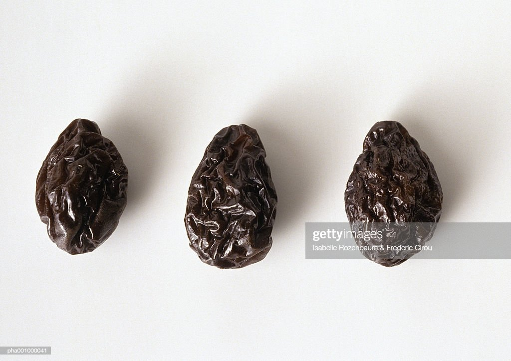 Three prunes against white background, close-up : Stockfoto