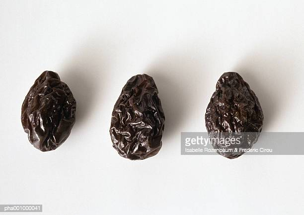 Three prunes against white background, close-up