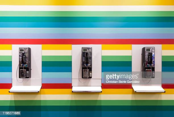 three public phones in front of a multicoloured striped wall, singapore. - christian beirle stock pictures, royalty-free photos & images