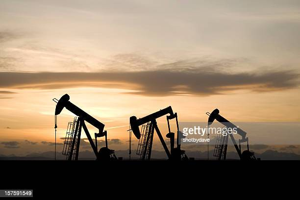three pumpjacks and a yellow sky - absence stock pictures, royalty-free photos & images