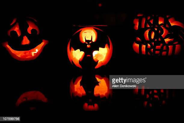 three pumpkins carved and glowing - halloween lantern stock photos and pictures