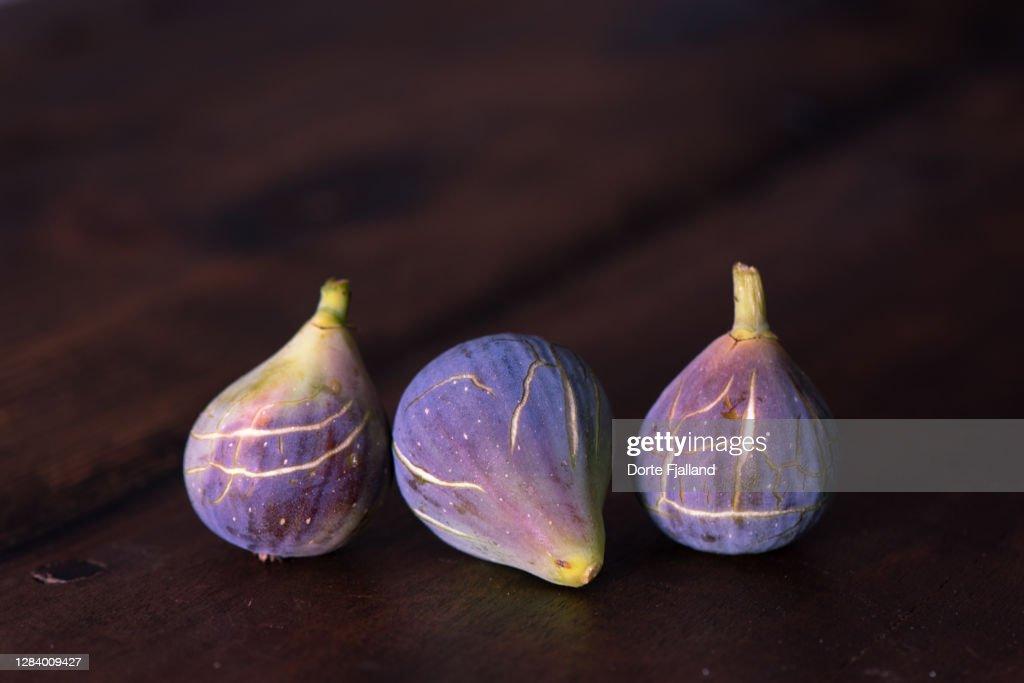 Three purple, ripe figs on a dark background : Foto de stock