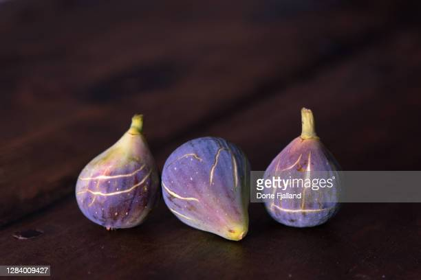 three purple, ripe figs on a dark background - dorte fjalland stock pictures, royalty-free photos & images