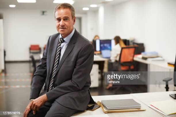 机の上に座っている中年男性の4分の3の長さのビジネス肖像画 - three quarter length ストックフォトと画像