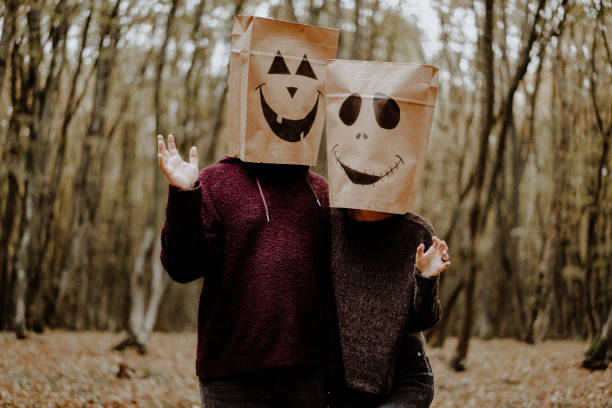 Three Quarter Length Of Couple Wearing Paper Bags Against Trees In Forest