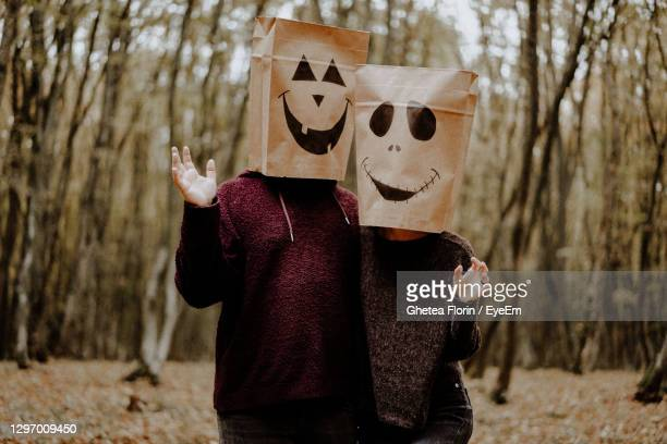 three quarter length of couple wearing paper bags against trees in forest - three quarter length ストックフォトと画像