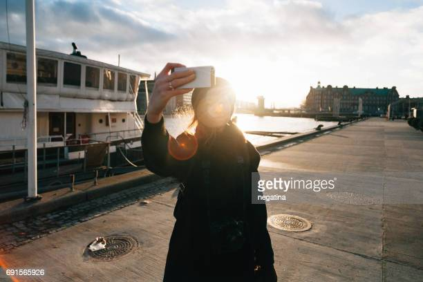 three quarter length of young woman in black coat takes a selfie on the waterfront in Copenhagen, Denmark