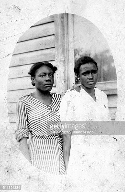 Three quarter length oval portrait of two young African American women standing in front of a house, the woman on the left in a striped dress, the...