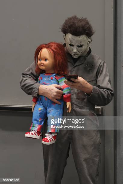 Three quarter length portrait of a comic book fan dressed as the character Chucky holding a doll and texting on a cellphone during New York Comic Con...