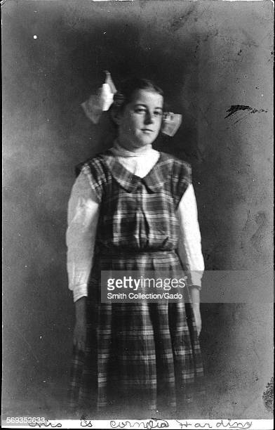Three quarter length portrait of a girl wearing a pinafore dress with a checkered pattern and a large bow in her hair June 23 1908