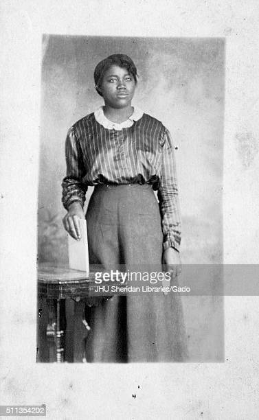 Three quarter length portrait of African American woman with a blank facial expression wearing a dark dress standing behind a table as she holds a...