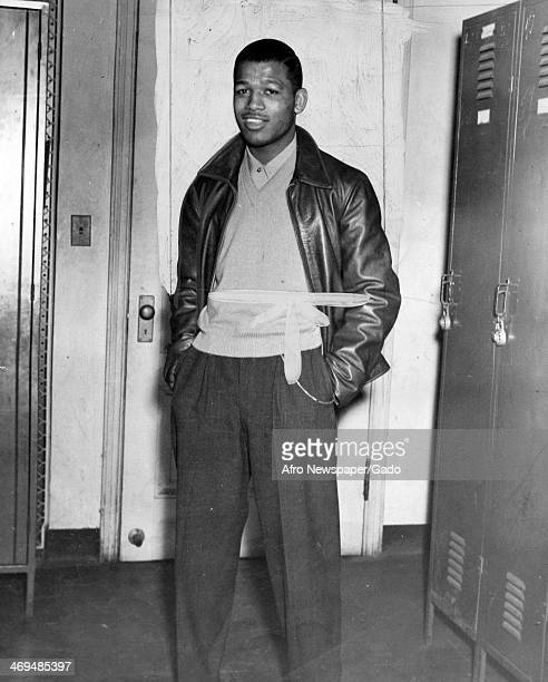 A three quarter length portrait of boxing champion Sugar Ray Robinson standing in a locker room wearing trousers shirt and sweater and a leather...