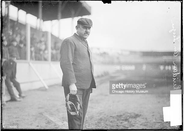 Three quarter length portrait of Jack Sheridan baseball umpire American League holding a mask standing near grandstand on the field at South Side...