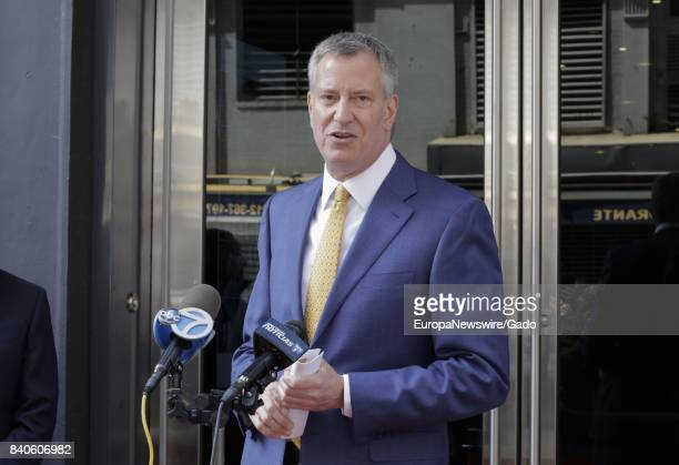 Three quarter length portrait of New York City mayor Bill de Blasio delivering a speech with microphones visible Greenwich Village New York City New...