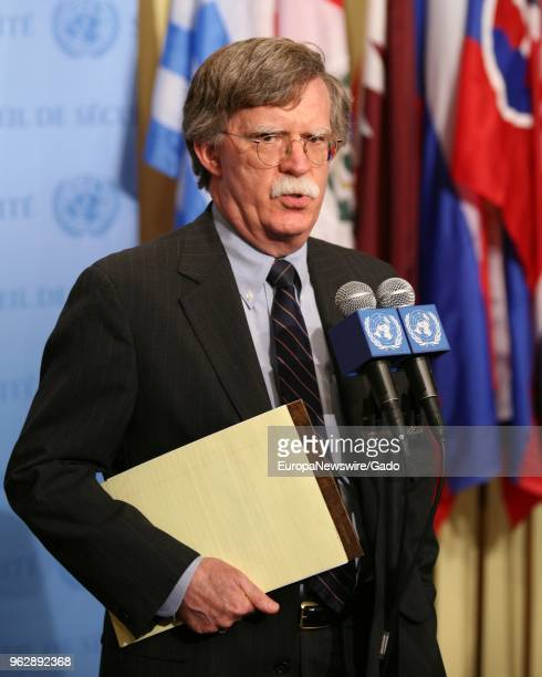 Three quarter length portrait of politician John Bolton speaking at the United Nations headquarters in New York City New York with colorful flags in...