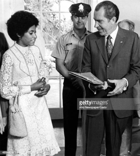 A three quarter length portrait of President Nixon at the White House being presented with a scroll by Wendy Johnson of 5931 Turner Street...