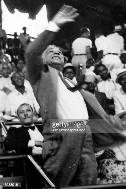 A three quarter length portrait of US representative Arthur Wergs Mitchell throwing the first ball at a baseball game between the Elks and Masons...