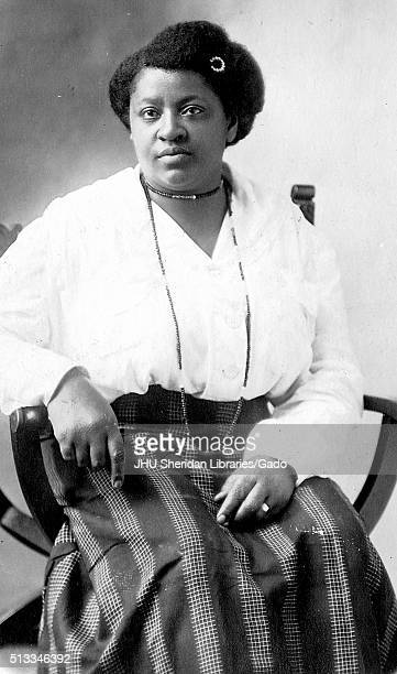 Three quarter length seated portrait, mature African American women, wearing dark skirt with patterns, light blouse, necklaces and hairpin, neutral...