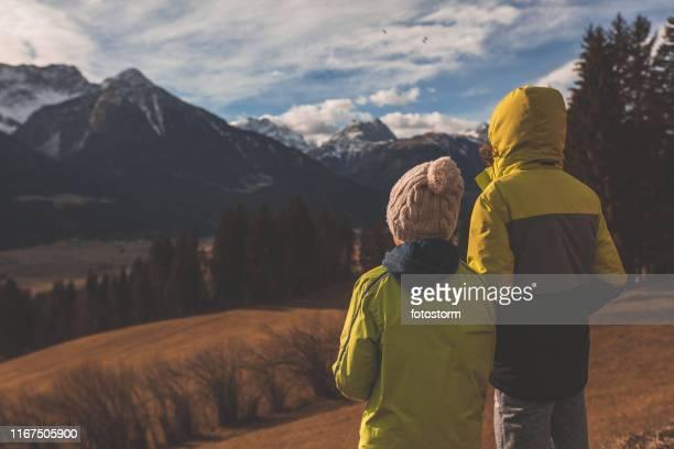 Three quarter length shot of teenage boys enjoying the sunset and the view of mountain range