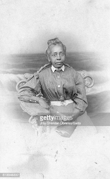 Three quarter length sitting portrait of elderly African American woman, wearing dark dress with light collar, belt and glasses, holding purse and...