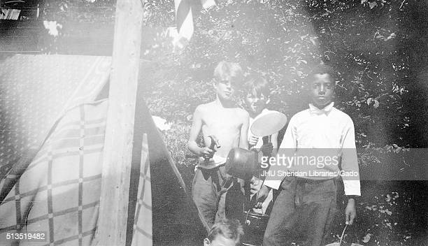 Three quarter length standing portrait of one African American boy with three white boys, African american boy wearing white shirt and dark pants...