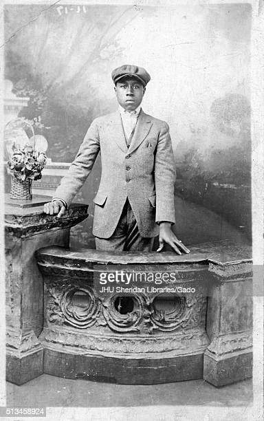 Three quarter length standing portrait of young African American man, wearing dark suit, light shirt and hat, standing at counter in front of...