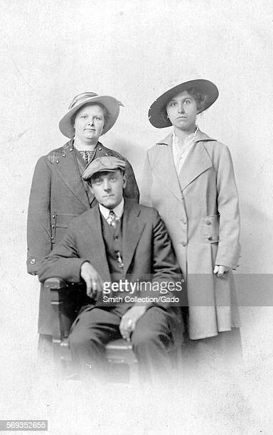 Three quarter-length portrait of a man wearing suit, tie, and a cap and sitting in a chair, 1950. Two women wearing coats and hats stand side by side...