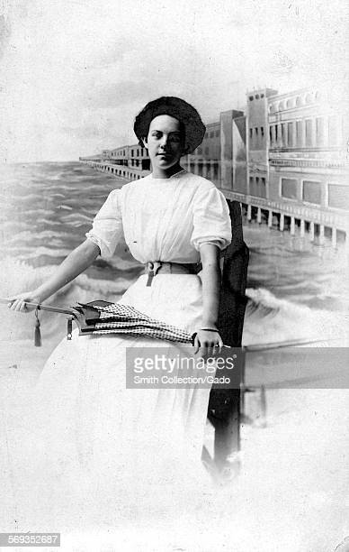 Three quarterlength portrait of a woman posing in front of a studio background depicting a seaside promenade 1950