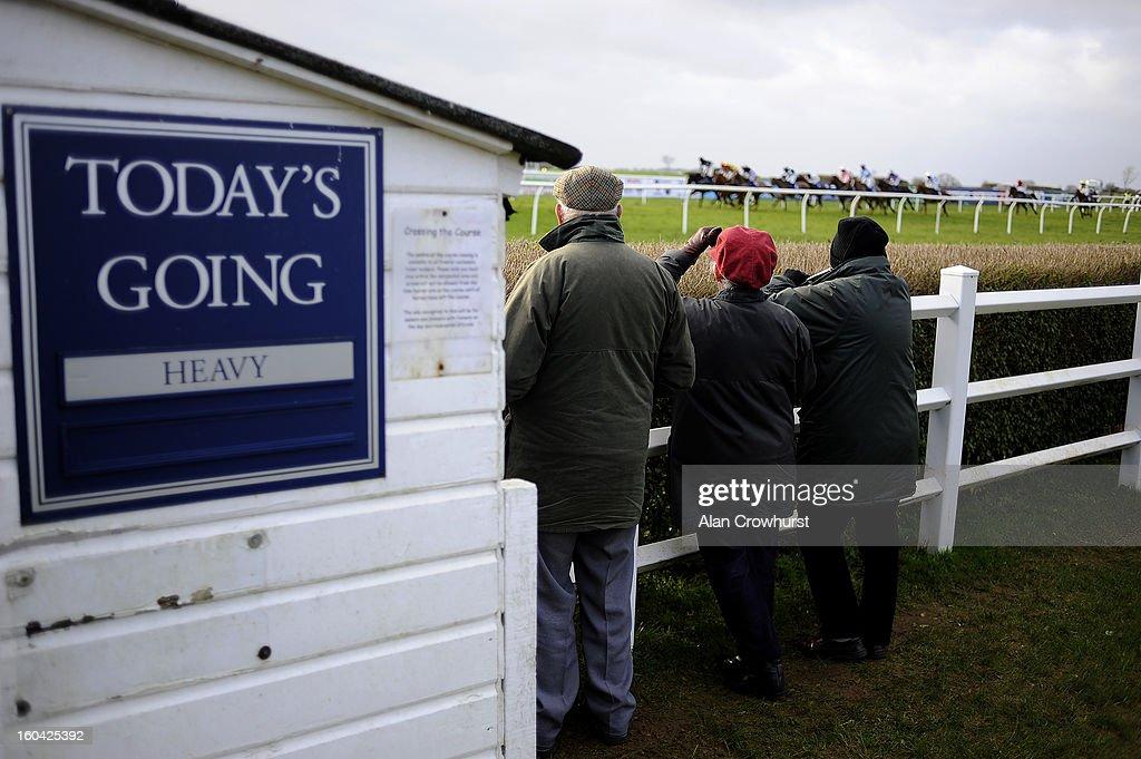 Three racegoers watch the runners pass at Wincanton racecourse on January 31, 2013 in Wincanton, England.