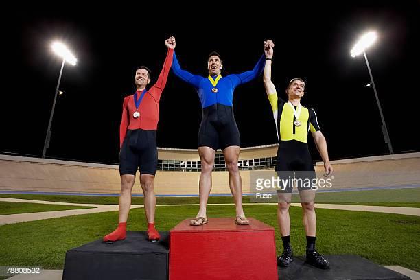 Three Racing Cyclists on Winner's Podium