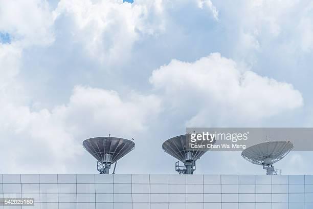 Three radio satellites and cloudy background