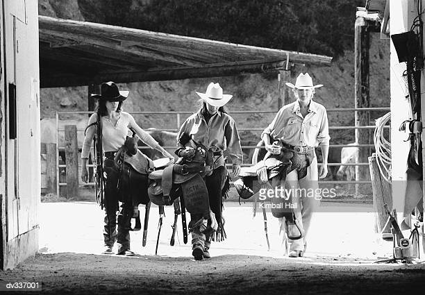 Three ranch hands with tack