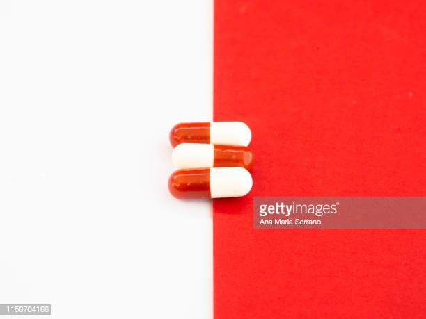 three red and white capsules - paracetamol photos et images de collection