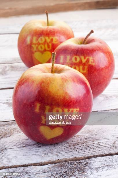 three red apples carved with hearts and the words 'i love you' - i love you photos et images de collection