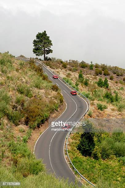 Three red car on a mountain road