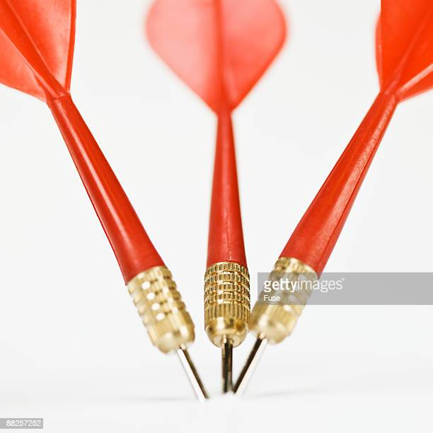 Three Red Darts Stuck Unright Close Together