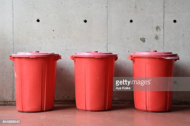 Three red dustbins