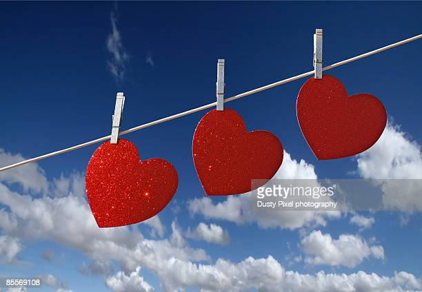 Three red hearts hanging on washing line