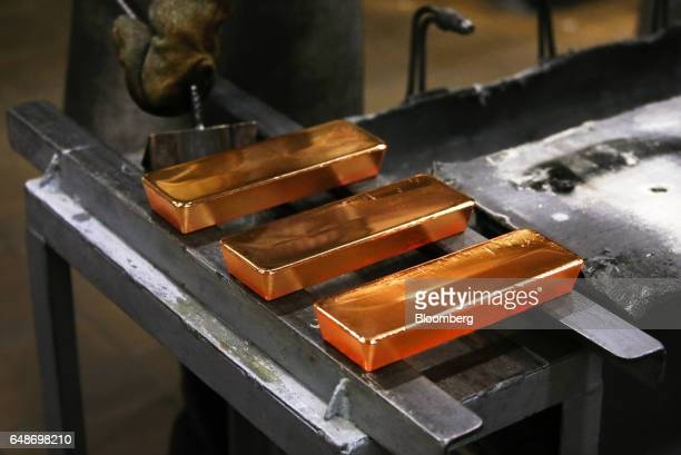 Three red hot gold ingots cool after being removed from casting molds by a worker in the foundry at the JSC Krastsvetmet nonferrous metals plant in...