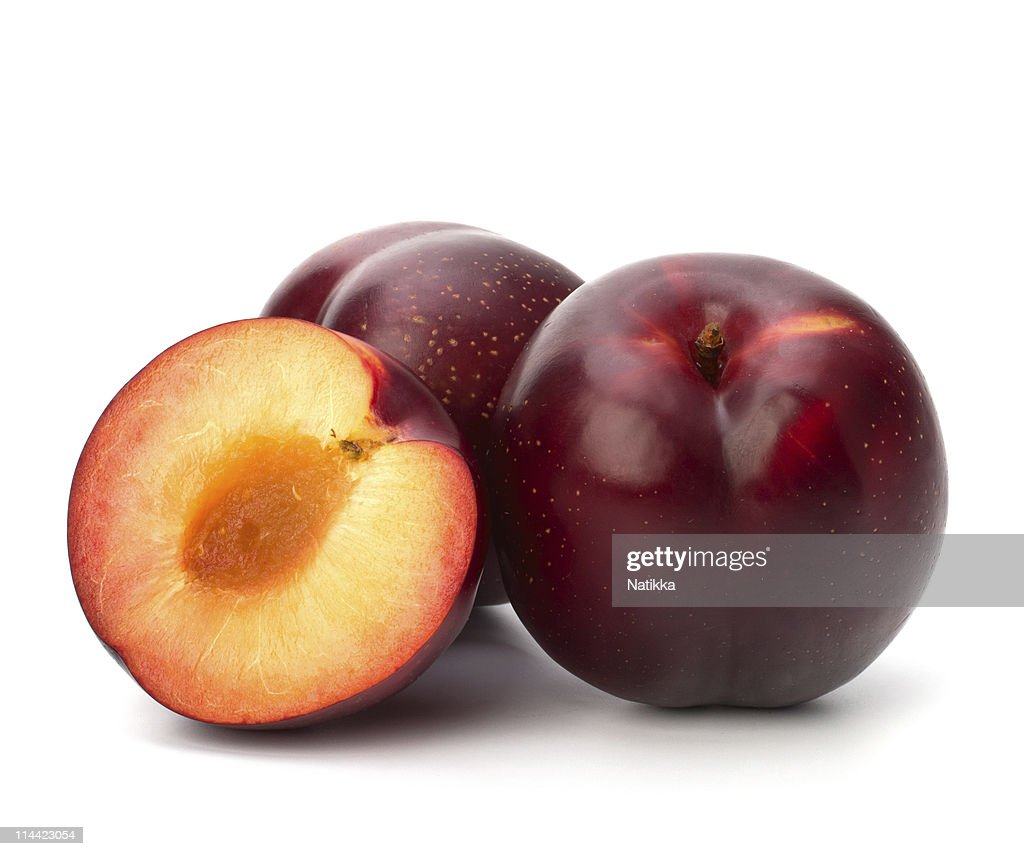 Three red plums - one cut in half and pitted - on white : Stock Photo