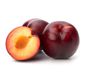 Three red plums - one cut in half and pitted - on white