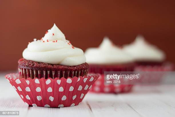 Three red velvet cupcakes on table