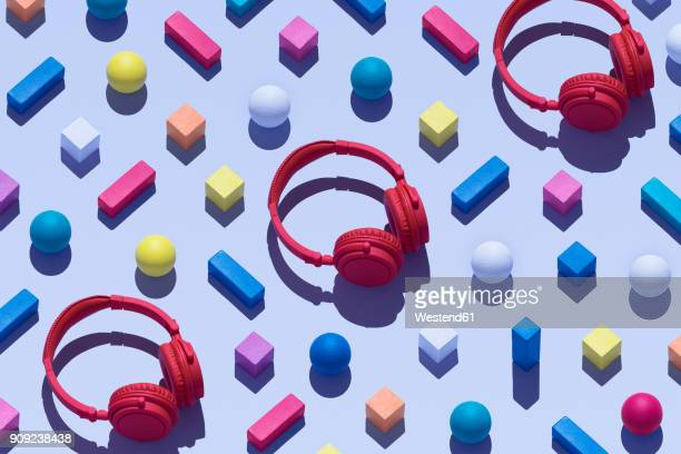 three red wireless headphones surrounded by geometric shapes, 3d rendering - 斜めから見た図 ストックフォトと画像