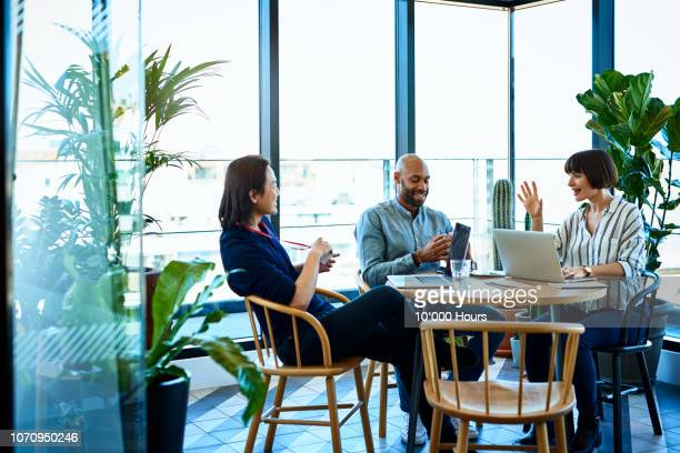 three relaxed business colleagues meeting in cafe - office stock pictures, royalty-free photos & images