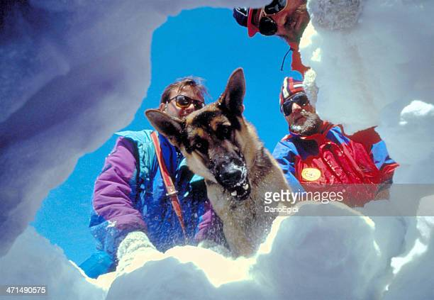 Three rescuers with dog in the snow, mountains in winter